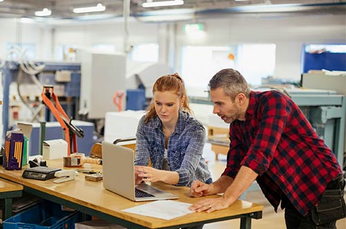 Man and woman in manufacturing looking at laptop